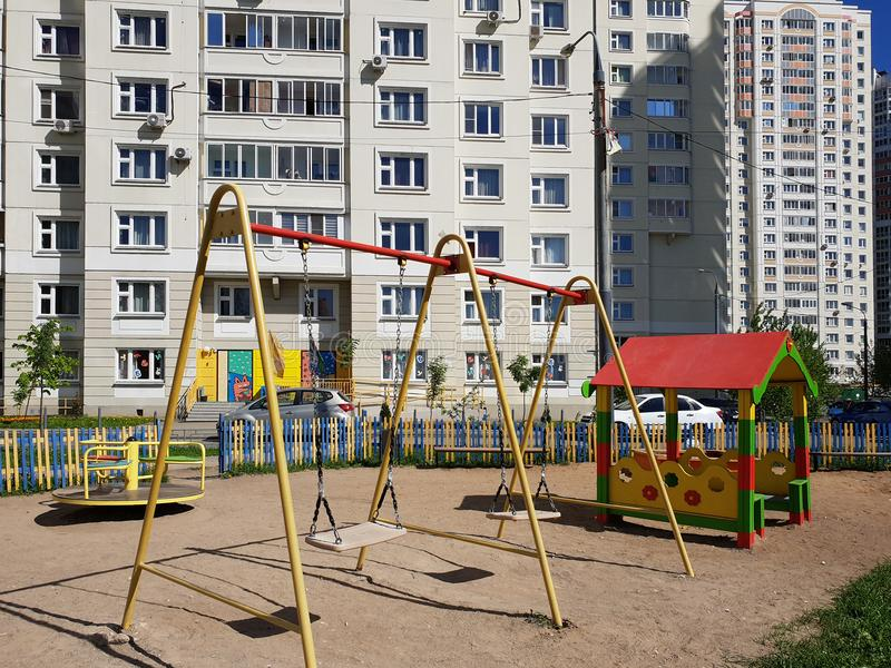 children& x27;s playground with swings in courtyard of residential building in the city, Russia royalty free stock photos