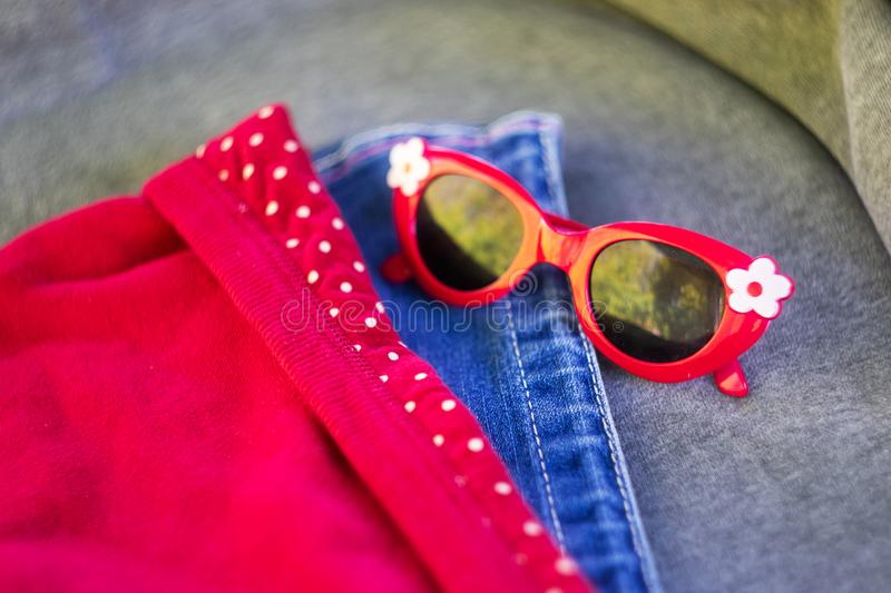 Children`s red glasses lie on the table next to the denim wardrobe. stock photos