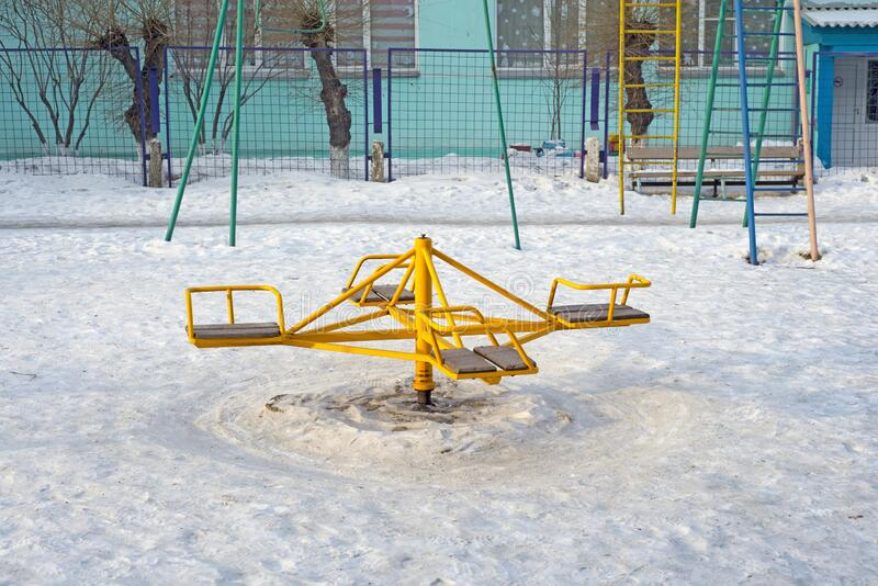 Children`s revolving carousels in the ordinary courtyard of an apartment building. Russia. Winter stock photography