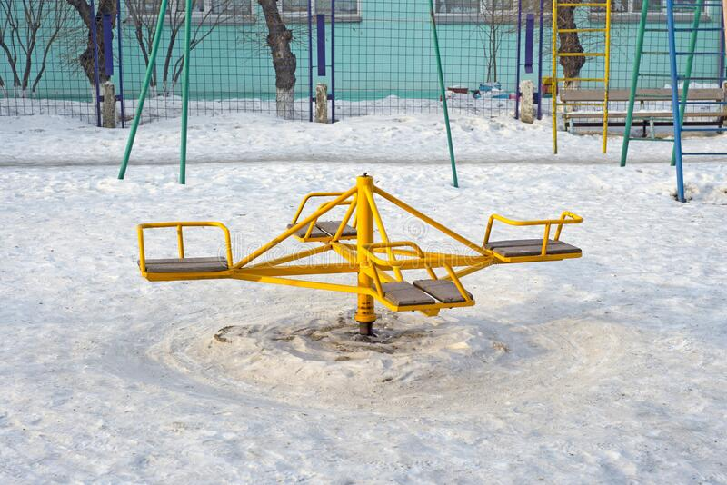 Children`s revolving carousels in the ordinary courtyard of an apartment building. Russia. Winter royalty free stock images