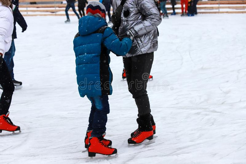 Children`s rink. The instructor teaches the teenager boy to skate. Active family sport during the winter holidays. stock image