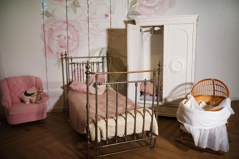 Children`s room with a white wardrobe, woven metal bed. Cradle for newborns in a beautiful interior stock photos
