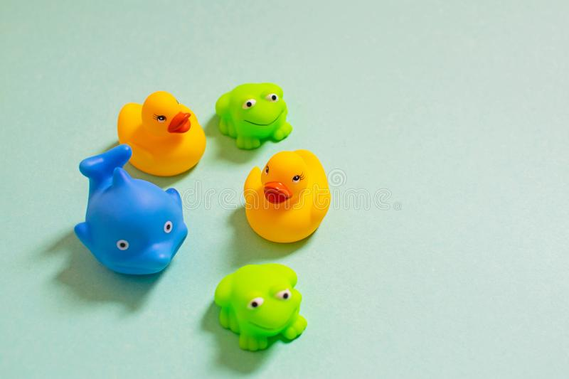 Children`s rubber bath toys on green background stock photo