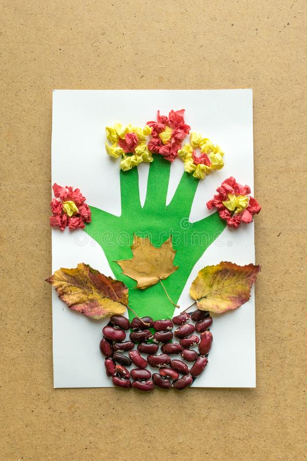 Children`s seasonal crafts from natural materials. Flower in pot from cereals, beans, dried leaves and colored paper Children`s seasonal crafts from natural stock photos