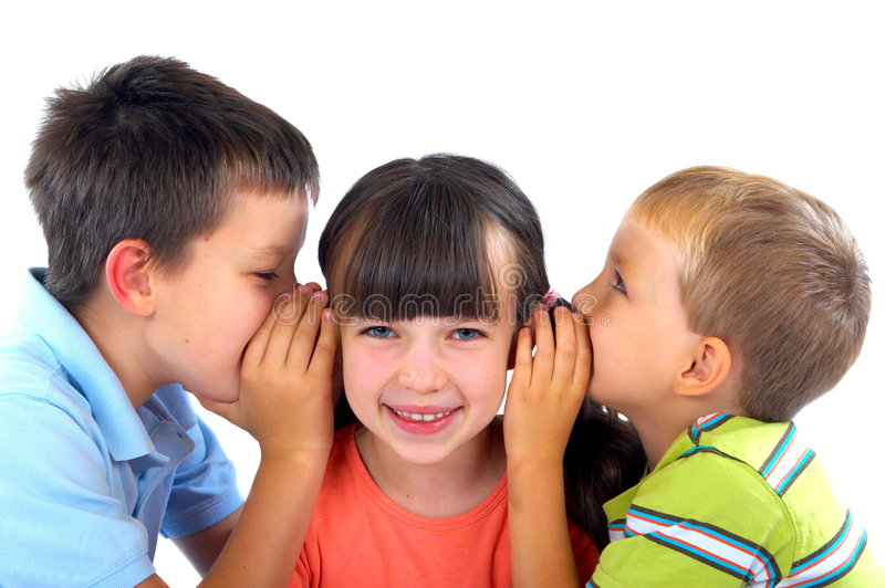 Children's secrets. Three children on a white background. The girl stands in the middle smiling as the two boys stand at her sides whispering into her ear with royalty free stock photography