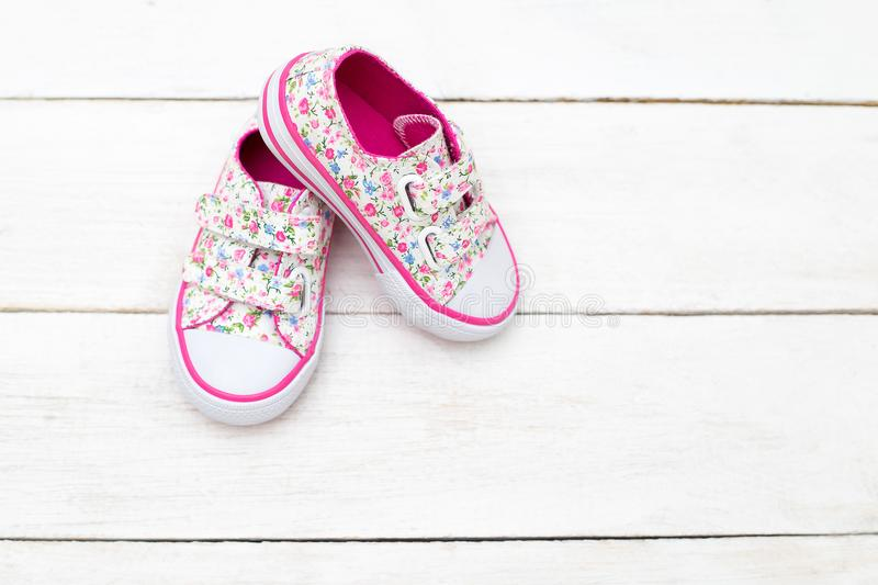 Children`s shoes for girls in florets on a wooden background. Fl royalty free stock image
