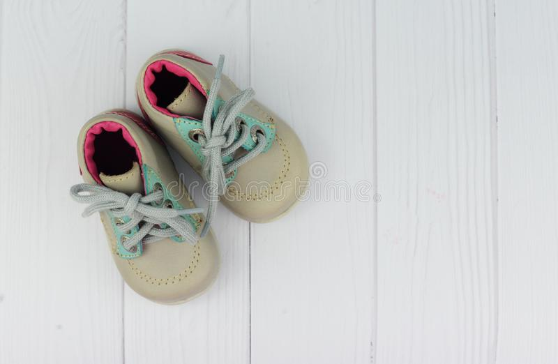 Children`s shoes gray boots on a background. With white wooden advertising store royalty free stock photography