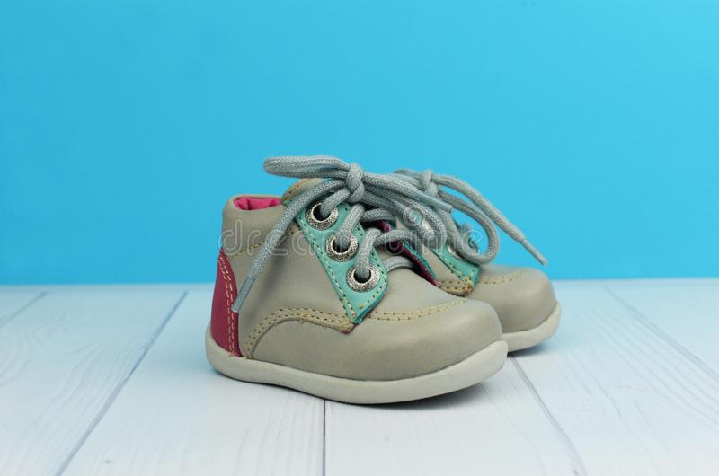 Children`s shoes gray boots on a blue background. With white wooden advertising store stock photos