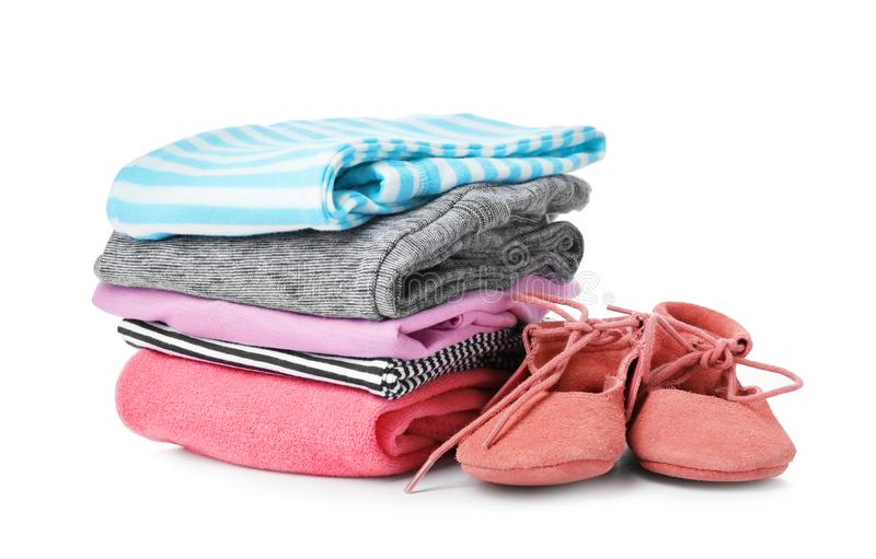 Children`s shoes and stack of clothes. On white background stock images