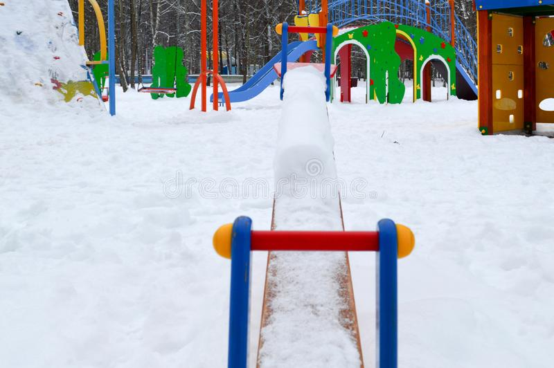 Children`s small toy swing balancer covered with snow on a children`s playground in the winter royalty free stock photos