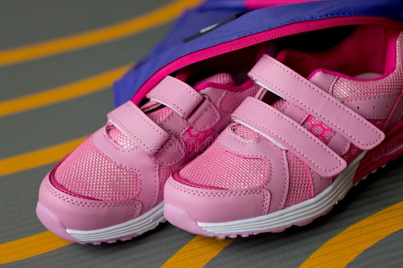 Children`s sneakers for girls and backpack lie on the carpet stock photography