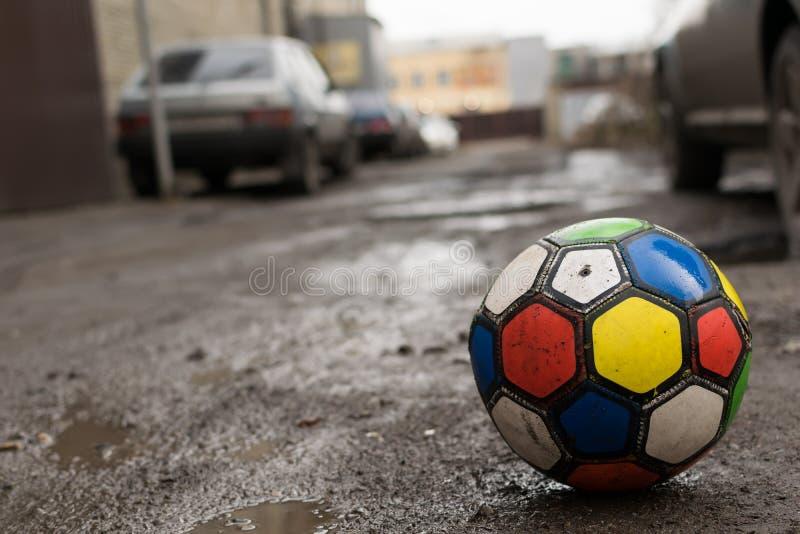 Children`s soccer ball lying on a dirty street stock image