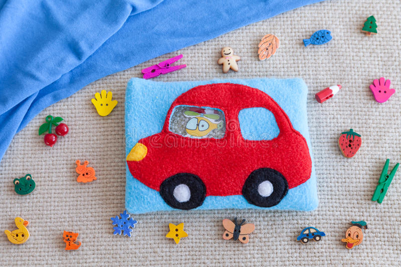 Children's soft toy red machine of colored fleece for motor development. Bag fleece filled with plastic beads and. Figurines on the background of scattered toys stock image
