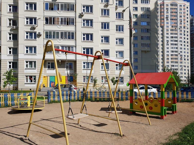 children& x27; s-Spielplatz mit Schwingen im Hof des Wohngebäudes in der Stadt, Russland lizenzfreie stockfotos