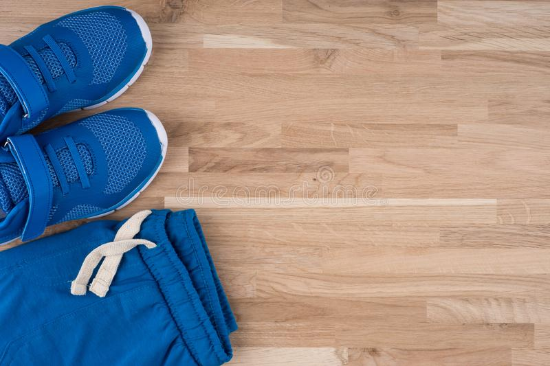 Children`s sports shorts with sneakers on a wooden table. royalty free stock photo