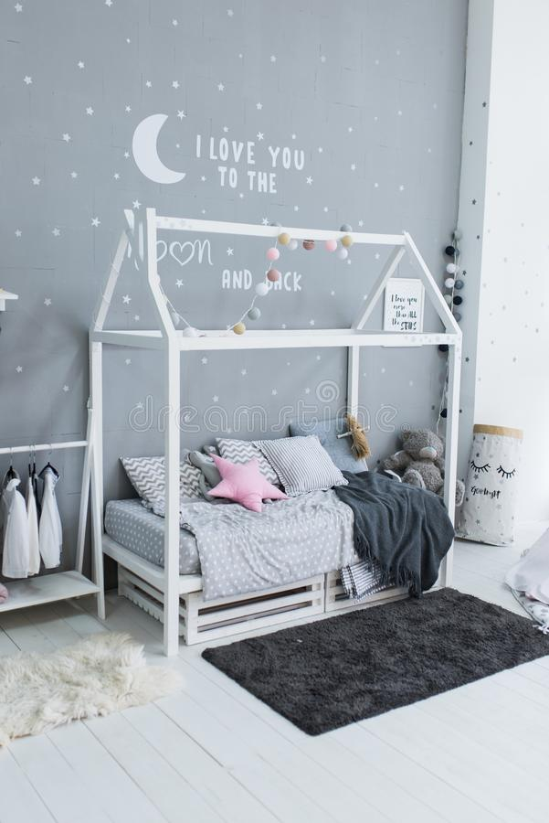 Children`s stylish bed in the form of a house. Scandinavian style boy`s bedroom with grey pillow and coverlet on handmade bed and royalty free stock photos