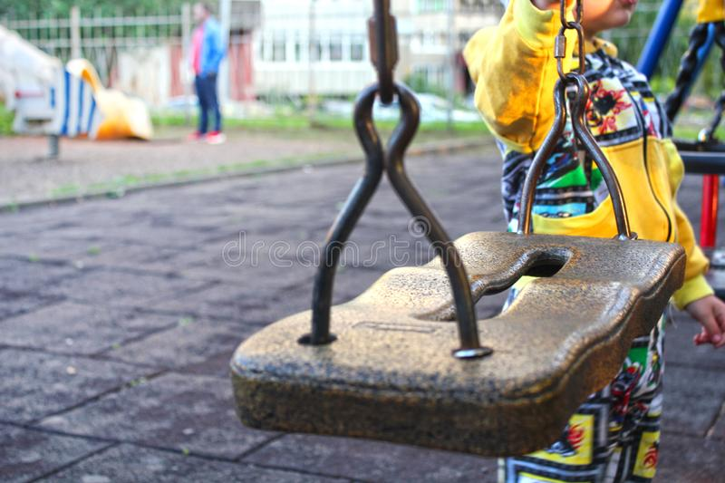 Children`s swing close-up. The boy stands next to the swing on the Playground. The theme of safety in playgrounds. stock image