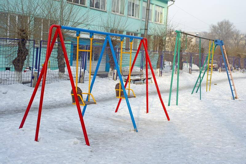Children`s swing on the playground in the ordinary courtyard of an apartment building. Russia. Winter royalty free stock photos