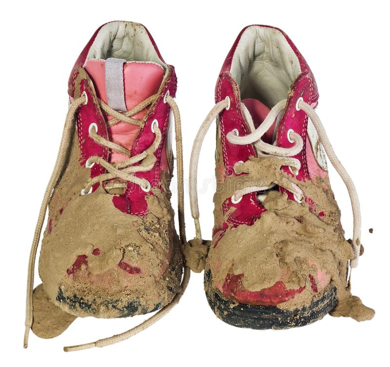 Children`s tiny shoes covered with mud. Dirty leggings for child. Ren`s feet in raspberry and white color isolated on a white background royalty free stock photos