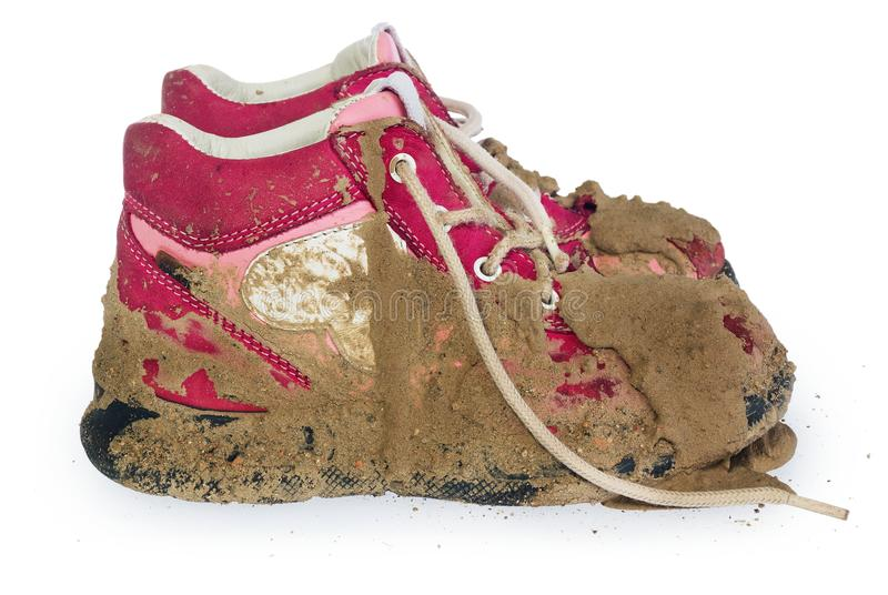 Children`s tiny shoes covered with mud. Dirty leggings for child. Ren`s feet in raspberry and white color isolated on a white background royalty free stock photo