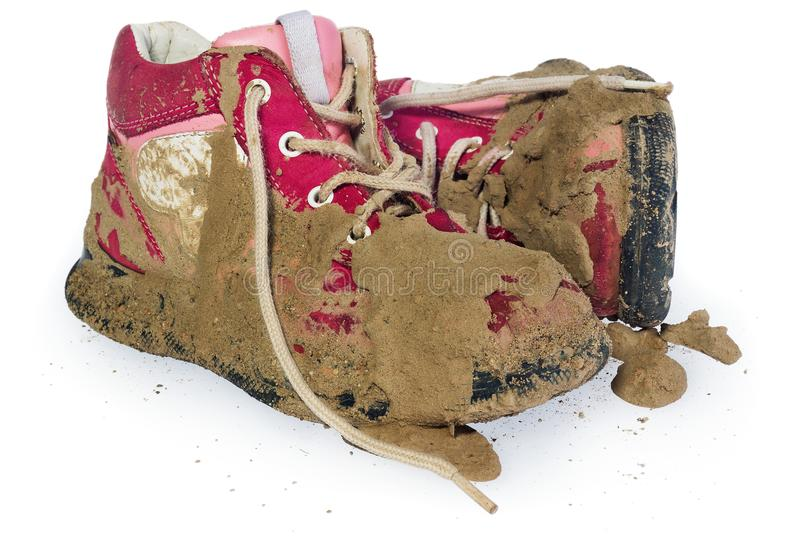 Children`s tiny shoes covered with mud. Dirty leggings for child. Ren`s feet in raspberry and white color isolated on a white background stock images