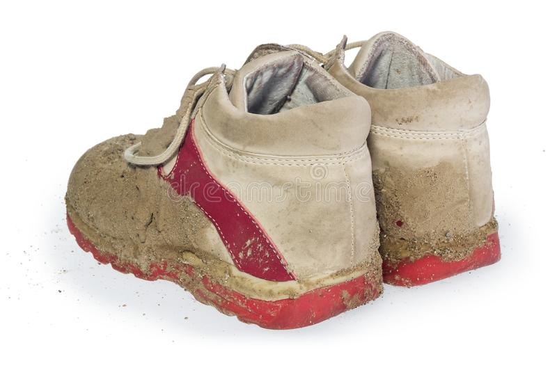 Children`s tiny shoes covered with mud. Dirty leggings for child. Ren`s feet in raspberry and white color isolated on a white background royalty free stock images