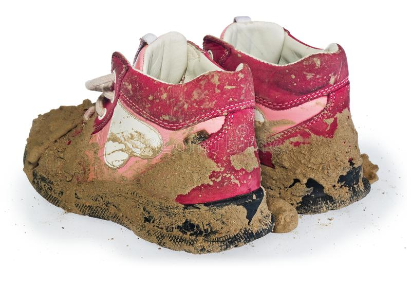 Children`s tiny shoes covered with mud. Dirty leggings for child. Ren`s feet in raspberry and white color isolated on a white background royalty free stock photography