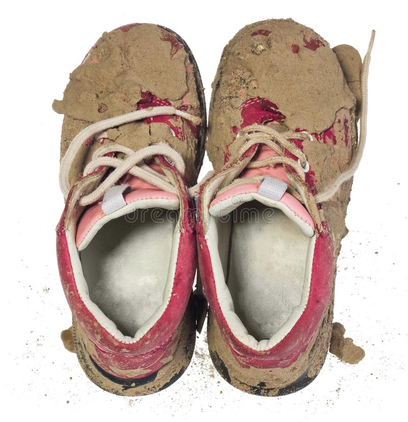 Children`s tiny shoes covered with mud. Dirty leggings for child. Ren`s feet in raspberry and white color isolated on a white background stock photos