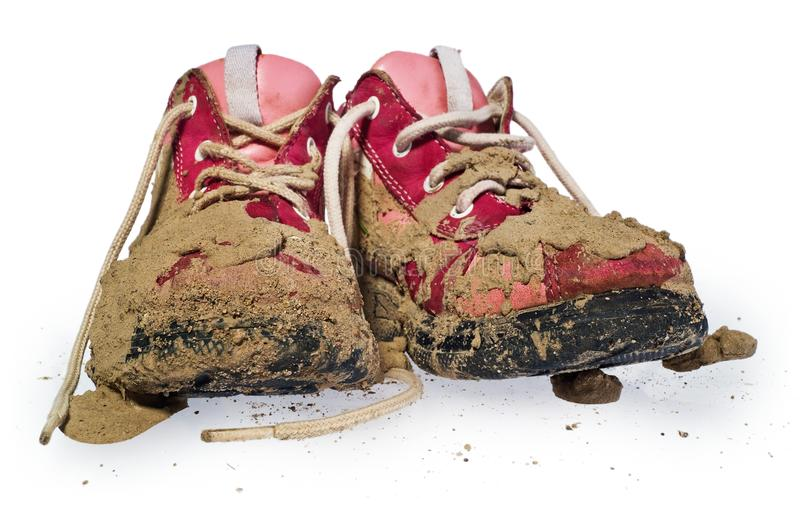 Children`s tiny shoes covered with mud. Dirty leggings for child. Ren`s feet in raspberry and white color isolated on a white background stock photo