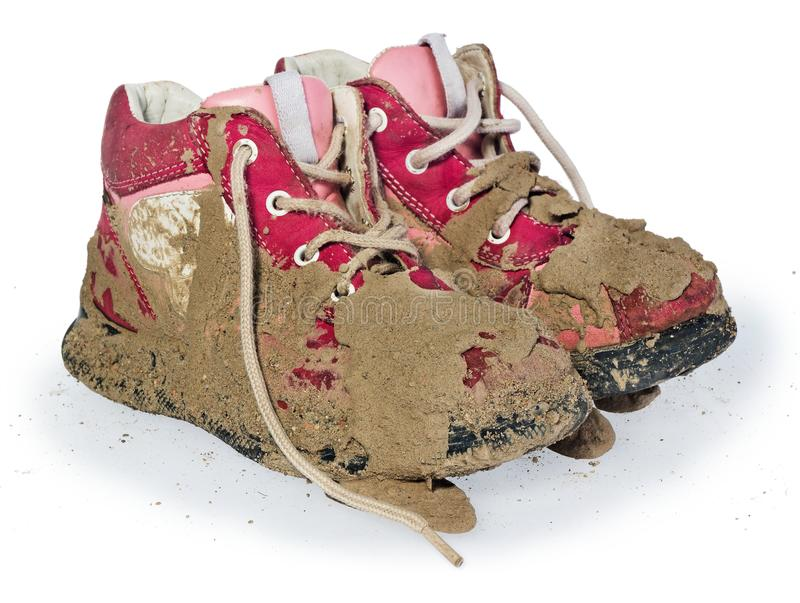 Children`s tiny shoes covered with mud. Dirty leggings for child. Ren`s feet in raspberry and white color isolated on a white background royalty free stock image