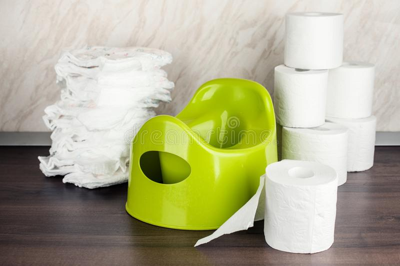 Children`s toilet pot green, nappies and toilet paper, the concept of the baby`s transition from diapers to the toilet. royalty free stock photos