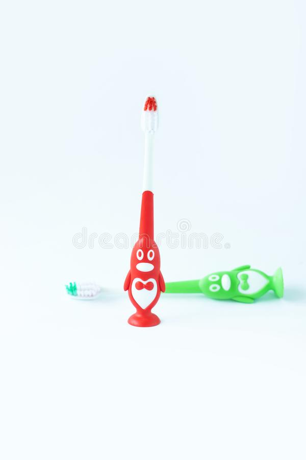 Children&-x27; s toothbrushes w postaci czerwieni i zieleni pingwinów na białym tle odizolowywającym fotografia royalty free