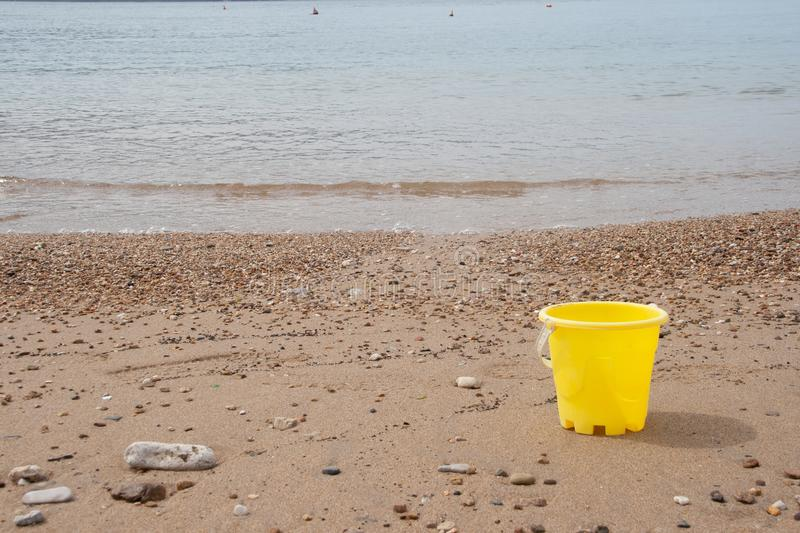 Children`s toy bucket in the sand at the beach royalty free stock photo