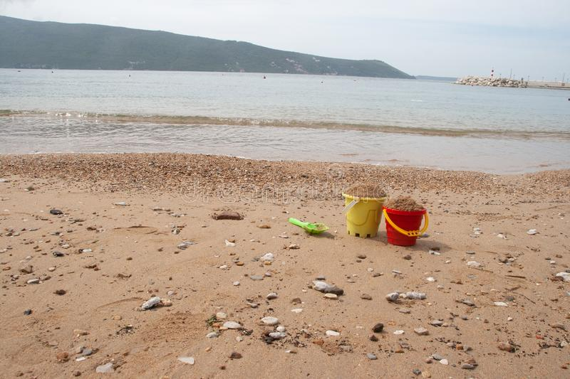 Children`s toy bucket in the sand at the beach stock photography
