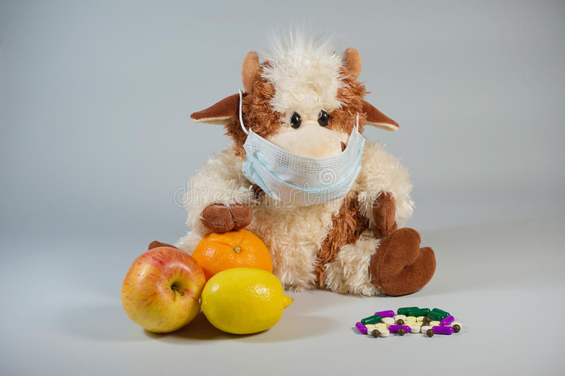 Children's toy bull in a medical mask with healthy fruits and va stock image