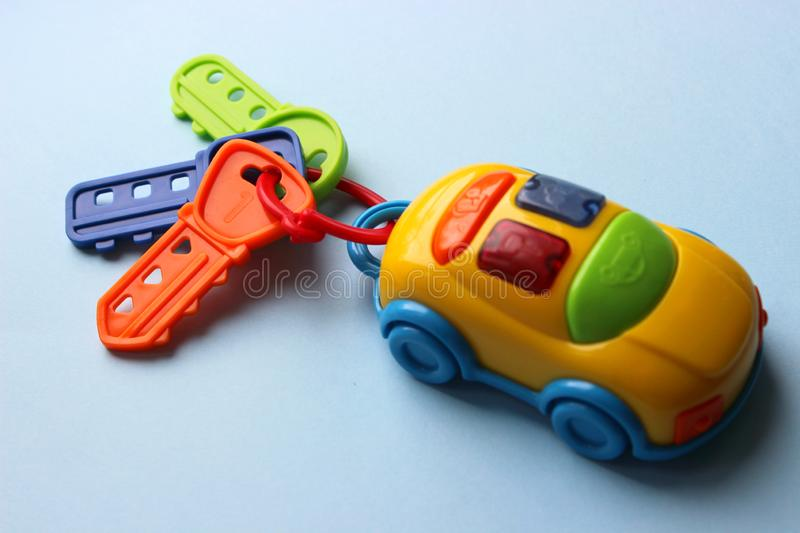 Children`s toy car with keys. Toy keychain from the car. Multi-colored key with keychain. stock photos