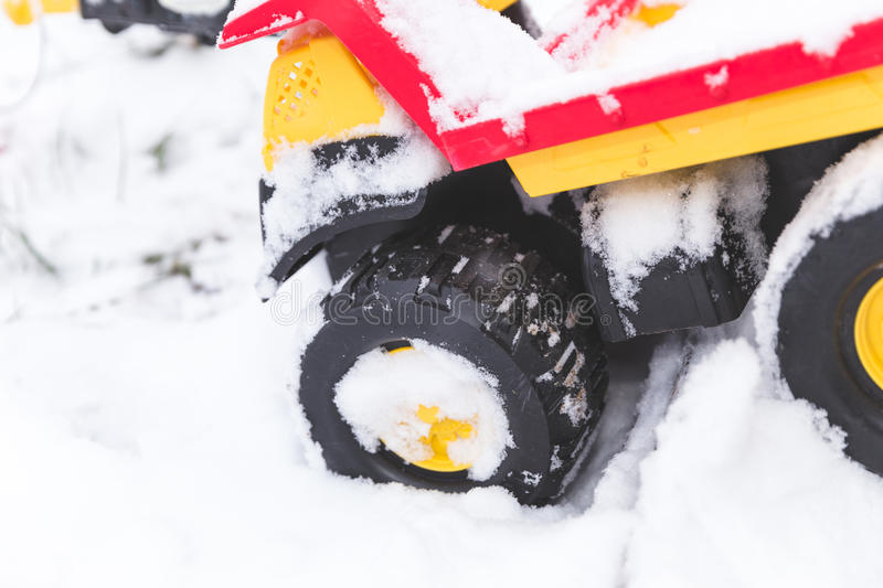 Children`s toy dump truck in winter snow. Colorful toy dump truck with large tires in deep snow royalty free stock photos