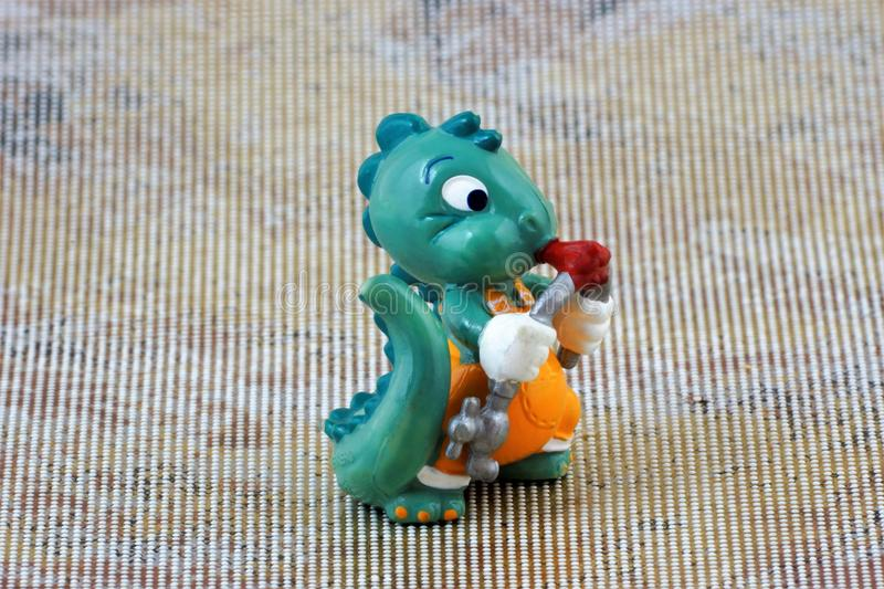 Children`s toy figure dragon Builder bends the pipe with the tongue of flame stock photos