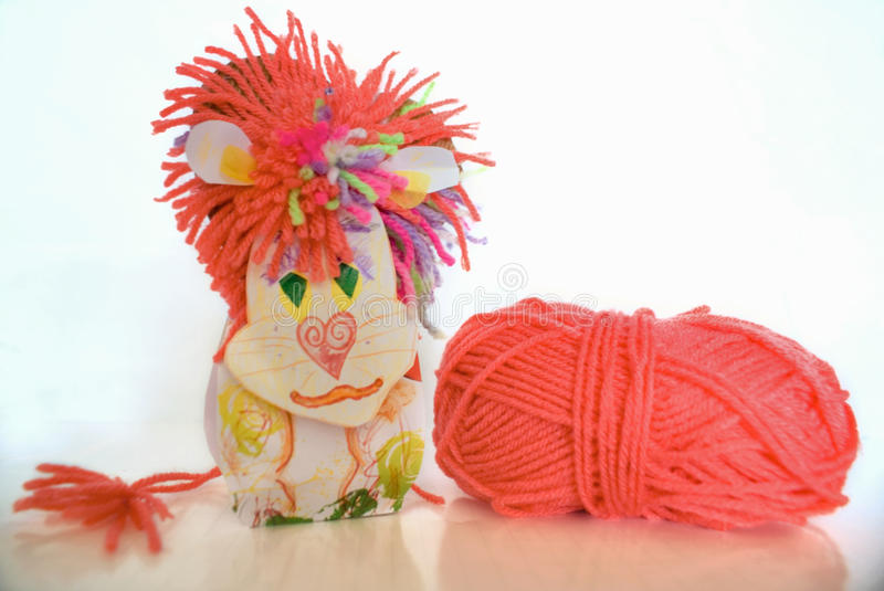 Children's toy lion hack with wool clew on white. Toy lion of coral wool and paper homemade, a ball of yarn on white background isolated stock photo