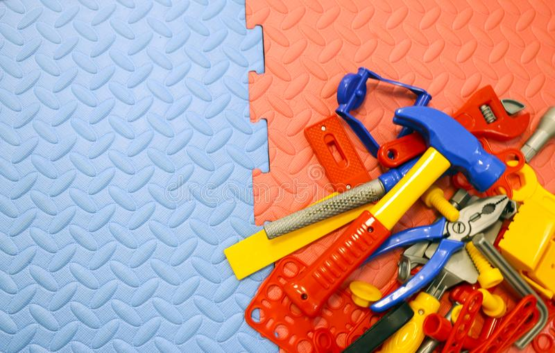 Children`s toy plastic tools builder and carpenter on textural background. Children`s toy plastic tools builder and carpenter on a textural background stock images