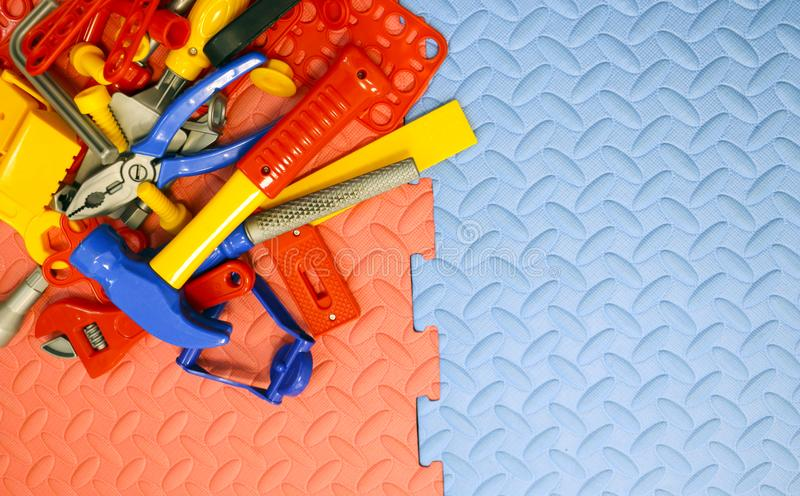 Children`s toy plastic tools builder and carpenter on textural background. Children`s toy plastic tools builder and carpenter on a textural background royalty free stock photography