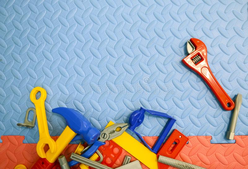 Children`s toy plastic tools builder and carpenter on textural background. Children`s toy plastic tools builder and carpenter on a textural background stock image