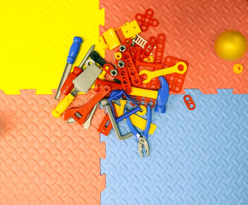 Children`s toy plastic tools builder and carpenter on textural background. Children`s toy plastic tools builder and carpenter on a textural background stock photos