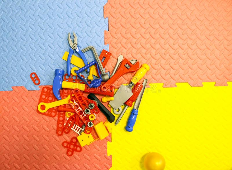 Children`s toy plastic tools builder and carpenter on textural background. Children`s toy plastic tools builder and carpenter on a textural background royalty free stock images