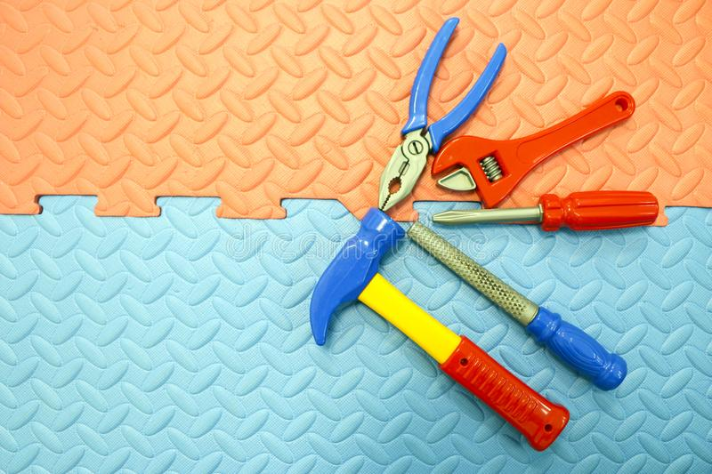 Children`s toy plastic tools builder and carpenter on textural background. Children`s toy plastic tools builder and carpenter on a textural background stock photography