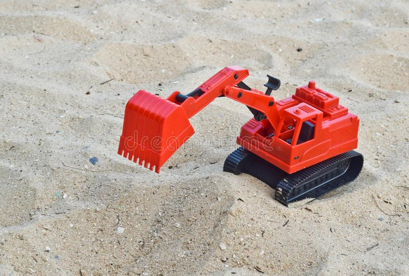 Children`s toy red excavator car on sand,industrial symbols.  royalty free stock photography