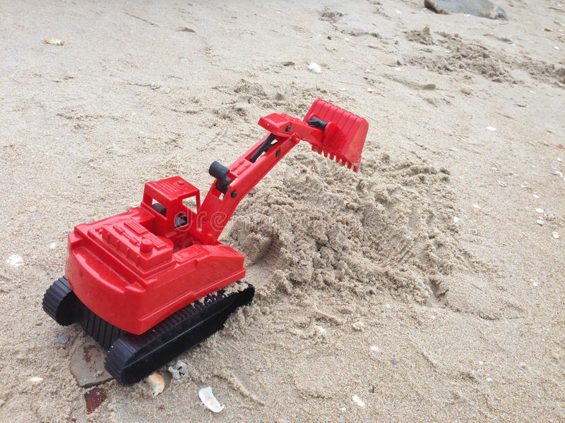 Children`s toy red excavator car on sand,industrial symbols.  royalty free stock images
