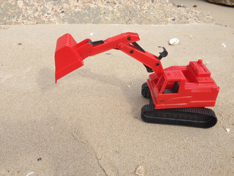 Children`s toy red excavator car on sand,industrial symbols.  royalty free stock image