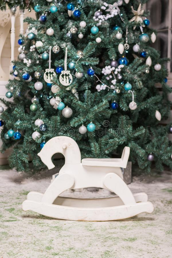 Children`s toy rocking horse near Christmas tree. gifts and holidays concept. horse rocking chair for children.Wooden stock photography