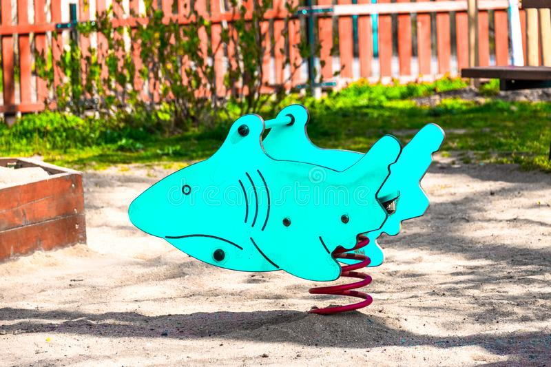 Children`s toy shark, blue color, on the playground for children stock photos
